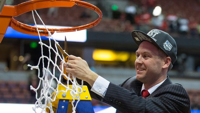 Patrick Herb cuts down a piece of the net after the Badgers qualified for the 2014 Final Four.