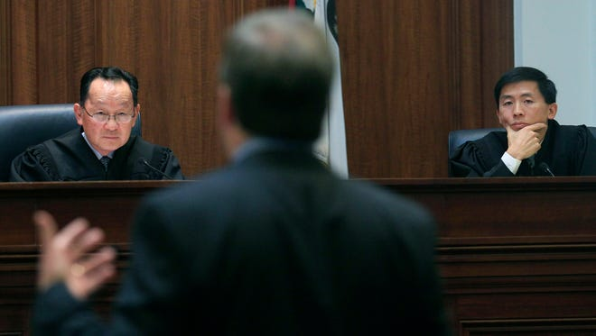 In this Nov. 10, 2011, file photo, Justice Ming Chin, left, and Justice Goodwin Liu, right, listen as Ross Moody of the San Francisco office of the attorney general speaks during a proceeding at the California Supreme Court in San Francisco.