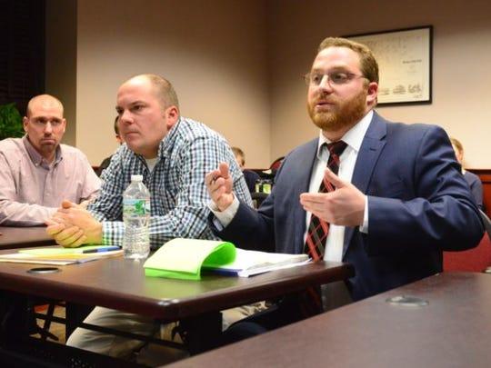 Attorney Jordan Handy, right, speaks on behalf of client