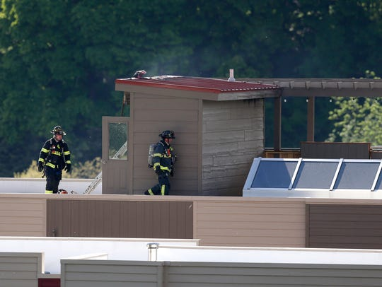 Firefighters work on the roof of a complex on the 200