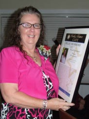 Nellie Drummond displays her award for Dedication and