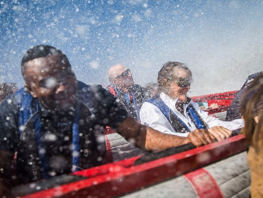 Claire Moses, center, laughs as water sprays over her