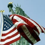 The American flag flies in front of the Statue of Liberty on Liberty Island.