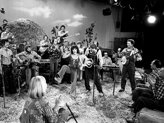 "Ruth Buzzi, center, veteran of TV's original ""Laugh-In,"" kicks out as he finishes a rousing rendition of ""May the Bird of Paradise Fly up Your Nose,"" with apologies to Little Jimmy Dickens, during a taping of the Hee Haw show Oct. 4, 1977."
