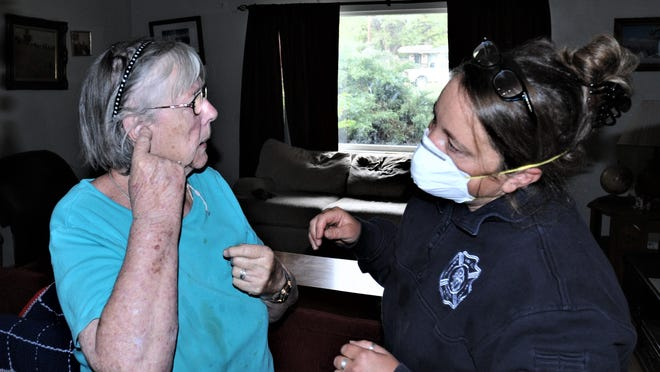 Pueblo Fire Department emergency medical officer Kelly Firestone, right, listens as Lesley Casillas explains a problem she is having with a hearing aid Tuesday.