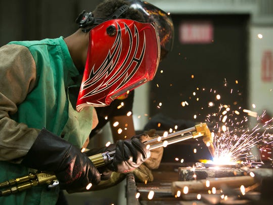 Caleb Ellis learns how to weld with assistance from