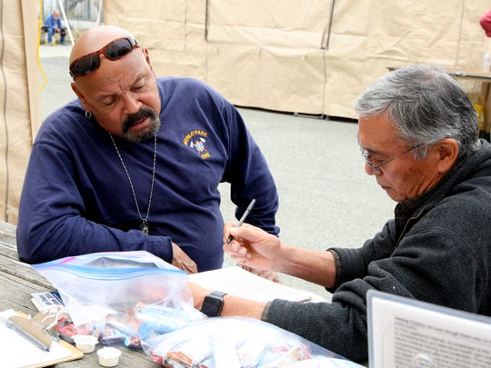 Veteran Daniel Gonzalez (left) of Modesto provides his information to a volunteer at the Monterey County Homeless Stand Down for Homeless Veterans on Saturday.