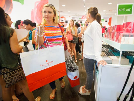 Kelli Abbiati, left, finishes shopping a day after Black Friday in 2015 at Kate Spade at Miromar Outlets in Estero. Black Friday sales have kicked off earlier this year.