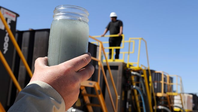 A jar holding waste water from hydraulic fracturing is held up to the light at a recycling site in Midland, Texas, in September. The drilling method known as fracking uses huge amounts of high-pressure, chemical-laced water to free oil and natural gas trapped deep in underground rocks. With fresh water not as plentiful companies have been looking for ways to recycle their waste.
