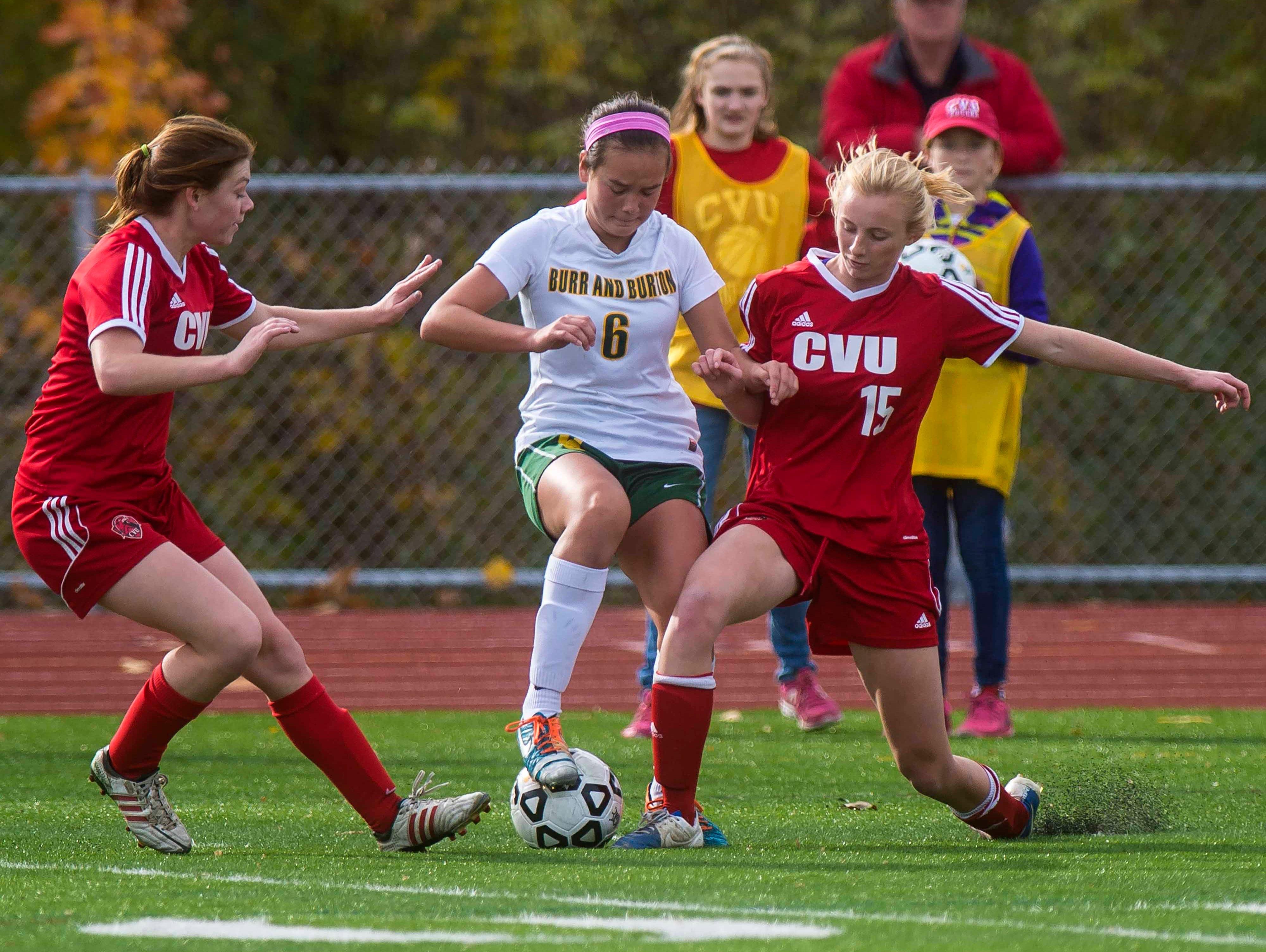 Burr & Burton's Georgia Lord, center, foots the ball between CVU's Megan Gannon, left, and Sierra Morton in the Division I girls soccer championship in Burlington on Saturday, October 31, 2015.