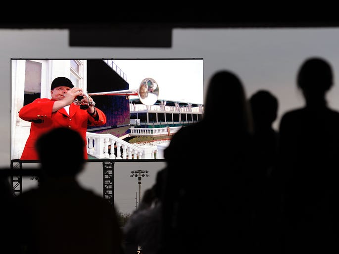 Race fans watch as bugelar Steve Buttleman plays the Call to the Post during the unveiling of the Big Board on Saturday at opening day of Churchill Downs. April 26, 2014