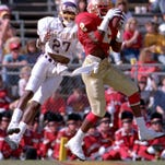 Deion Sanders makes an interception in front of a receiver.