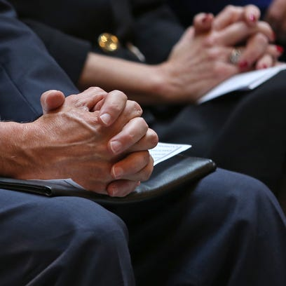 Governor Mike Pence holds his hands together in prayer