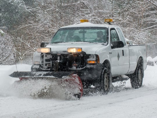 A Wicomico County plow truck drives on Schumaker Ln
