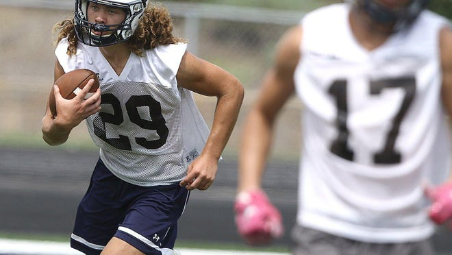 Fairless' Coltin Colucci looks for running room as Conner Durant looks to block during practice on Aug. 17.