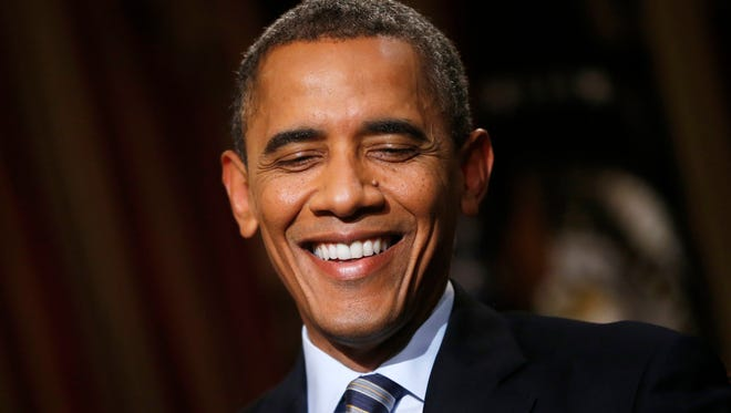 In this 2013 photo. Obama smiles during an exclusive interview with The Associated Press in the White House library in Washington.