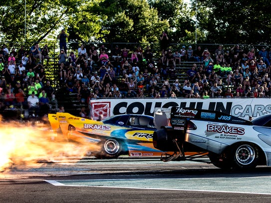 Jet funny cars prepare to race down the track at National
