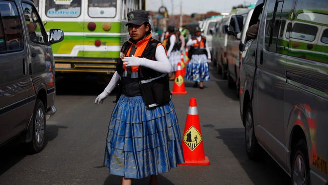 An Aymara woman cops directs traffic on the streets of El Alto, Bolivia. The women wear the bright petticoats and shawls of indigenous women in the Andes, called cholitas in Bolivian slang