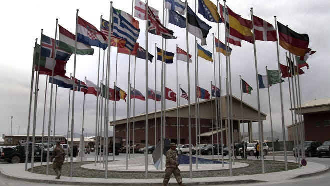 NATO Soldiers walk under country member flags at a NATO base at Kabul  International Airport in Kabul, Afghanistan, April 30.