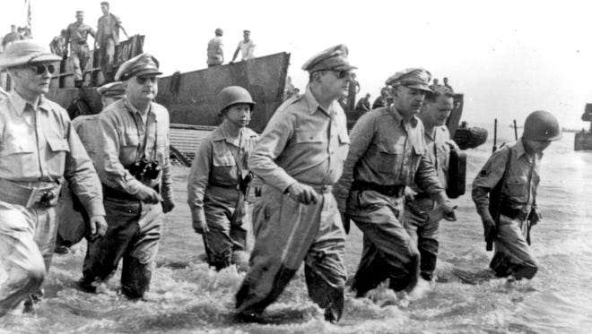Gen. Douglas MacArthur (center) vowed to one day return to the Philippines after the Japanese invasion, a feat he accomplished with his officers and Sergio Osmena, president of the Philippines in exile (far right) at Leyte on Oct. 20, 1944.