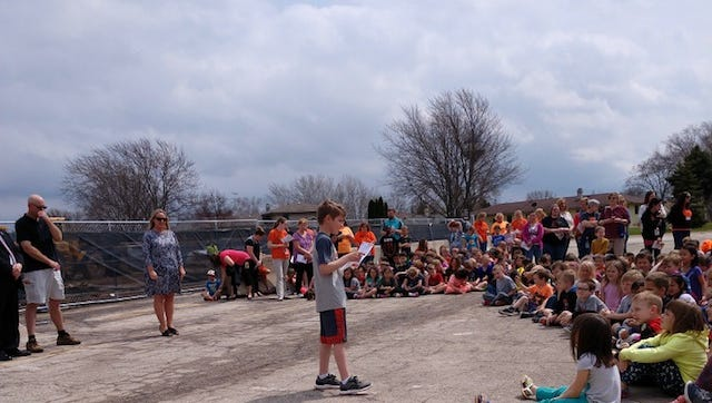 Second grade student Eli Zar addresses the crowd at the Friendship Learning Center building ceremony.