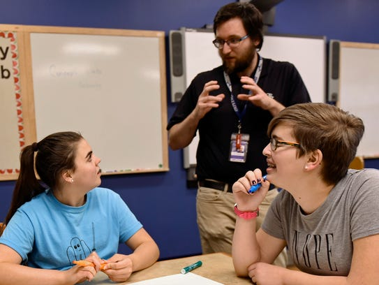Instructor Paul Schlabach, standing, helps students,