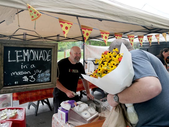 Dan Prasch of Mad Moose Pizza helps a customer at the