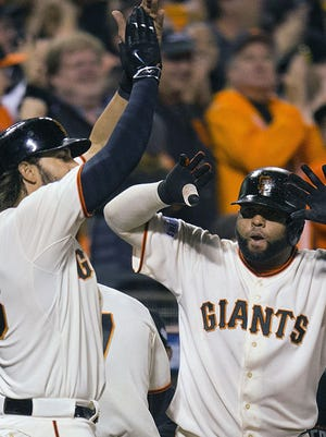 Giants pinch hitter Michael Morse, left, and Pablo Sandoval celebrate scoring on Joe Panik's two-run double in the seventh inning of Game 4 of the World Series Saturday in San Francisco.