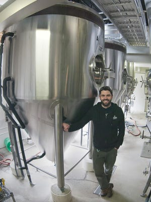 Grant Pauly, founder and brewmaster of 3 Sheeps Brewing Co., stands by one of his brewing kettles.