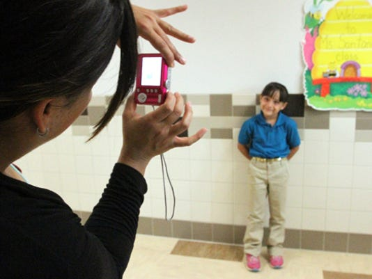 Rudy Gutierrez El Paso Times Kaitlin Reza gets her picture taken outside her new classroom by her mother, Cynthia Licon during opening day of the James P. Butler Elementar School in fare East El Paso Monday.