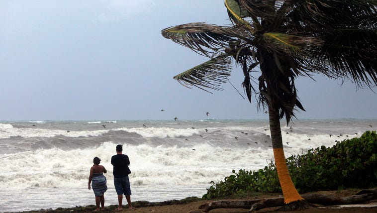 A couple looks out at a rough sea as Tropical Storm