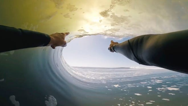 In this image made from video provided by Chris Rogers, surfer Koa Smith points at a wave during his two-minute ride off the coast of Namibia on the western shore of Africa. Smith rode the wave for nearly a mile and stayed upright as he traveled through eight barrels--the hollow formed by the curve of the wave as it breaks over the surfer's head.