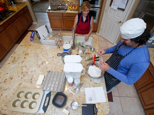 Matt Cottle, owner of Stuttering King Bakery, chats with his mother, Peg, as he works on a batch of muffins in his parents' kitchen in Scottsdale.