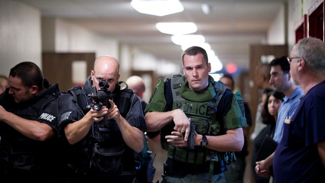 Cherry Hill police officers walk toward a classroom during a live shooter simulation at Cherry Hill High School, Wednesday, August 6, 2014 in Cherry Hill.