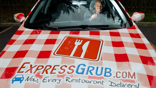 Mohammed Oloko, founder of new ExpressGrub delivery service, poses for a portrait with one of his delivery cars, Tuesday, August 12, 2014 in Cherry Hill.