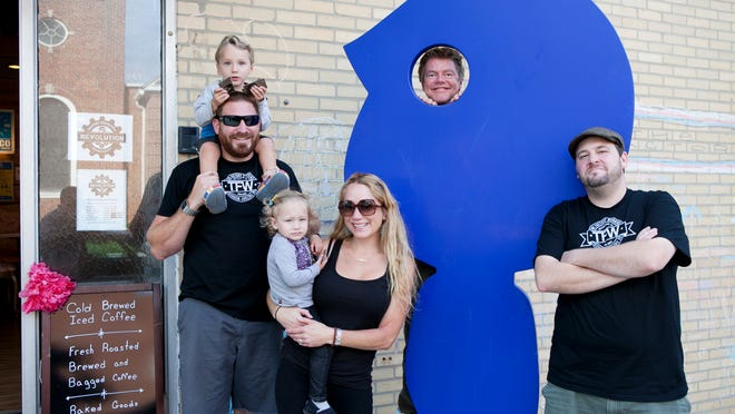 Tom Marchetty, owner of The Factory in Collingswood, poses in front of the statue with his son Billy, 2, wife Amy Marchetty, Bella, 2, Steve McFadden, who owns Revolution Coffee Roasters, and Marcus Darpino of Wildfire Radio on Thursday.