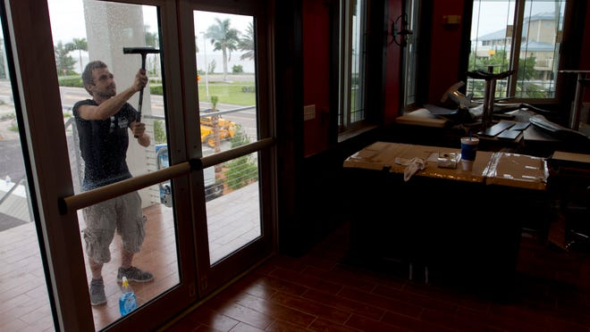 Brad Dollard cleans the doors for SS Hookers, a new restaurant is soon to open. The restaurant has a view overlooking San Carlos Bay and the Sanibel Causeway.