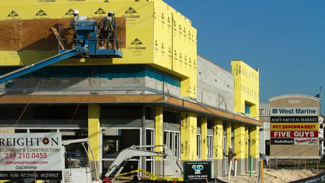 Workers put up plywood on the exterior of a Bank United branch at College Parkway and U.S. 41.
