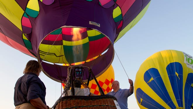 "Barbara Stokoe, left, and Greg McCarty, right, help Steve Stokoe of Tampa take off in his balloon named ""Sail Away"" during the 3rd annual Balloons Over Paradise Festival at Seminole Casino in Immokalee on Saturday."
