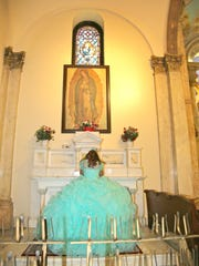 The quinceanera prays to the virgencita, the Lady of Guadalupe, during her mass at St. Paul's.
