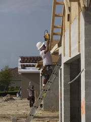 Fernando Marquez works on a new home being built in the Watermark Community in Fort Myers.