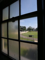 The athletic field at Gorton High School is visible through one of the few clear window panes in a classroom.