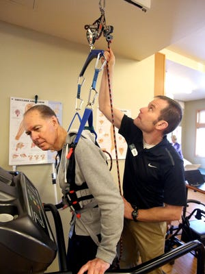 Mel Wiggers, left, a patient at Northwest Rehab Associates, works with physical therapist Mike Studer on Friday, March 6 , 2015, in Salem, Ore. Wiggers, who is battling Parkinson's  disease uses a harness on a treadmill that stabilizes him during his treatment.