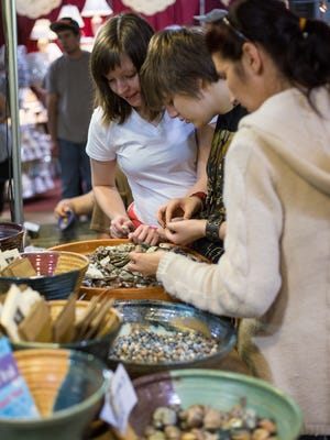 Local residents take a look at an artisan's goods at a Sugarloaf Crafts festival in 2014.