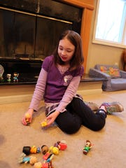 Amanda Houser plays with Charlie Brown figurines at