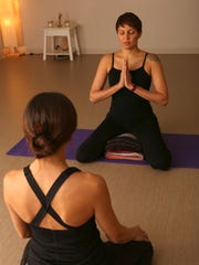 Instructor Dee Yergo, right, demonstrates a mediation pose, a powerful practice to calm the mind.