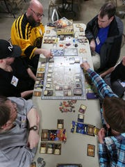 """FILE - A group of players play the """"Lords of Waterdeep"""" at the 16th Fire and Ice Game Convention in 2016."""