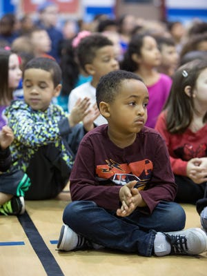 Mohamed Abubakar, 5, of West Des Moines, applauds Thursday as the Indian Hills Junior High School jazz band performs for students at Clive Elementary School in Windsor Heights.