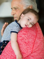 Mark Medoff holds his 2-year-old granddaughter Hope E. Harrison at his home. Hope was born with Trisomy 18 chromosomal anomaly.