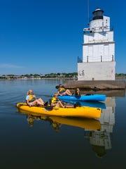 The Ludtke family peddle kayaks past the lighthouse
